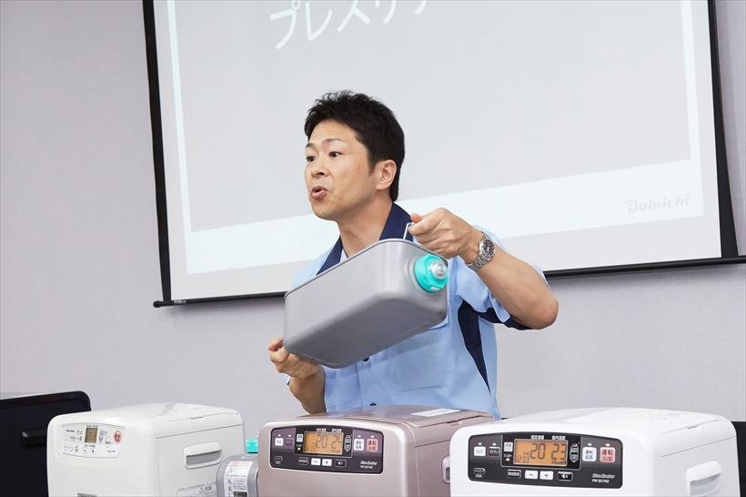 ↑「Wとって」の解説をする同社営業部の統括マネージャー、中嶋純一氏。「Wとって」は、2か所に取っ手を設けることで、両手でタンクが持てるのが便利です
