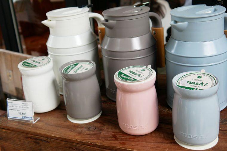 ↑初のタンブラーサイズである9月発売の「mosh!タンブラー(ヨーグルト)」は、ヨーグルト瓶がモチーフ。こちらはセラミック塗装が施され、まるで陶器のような質感で、持ちやすいサイズ感も特徴です。価格は250ml・1800円(税抜)。奥は底部に回転台が付いた「mosh!卓上ポット タンク」。1L・3800円(税抜)