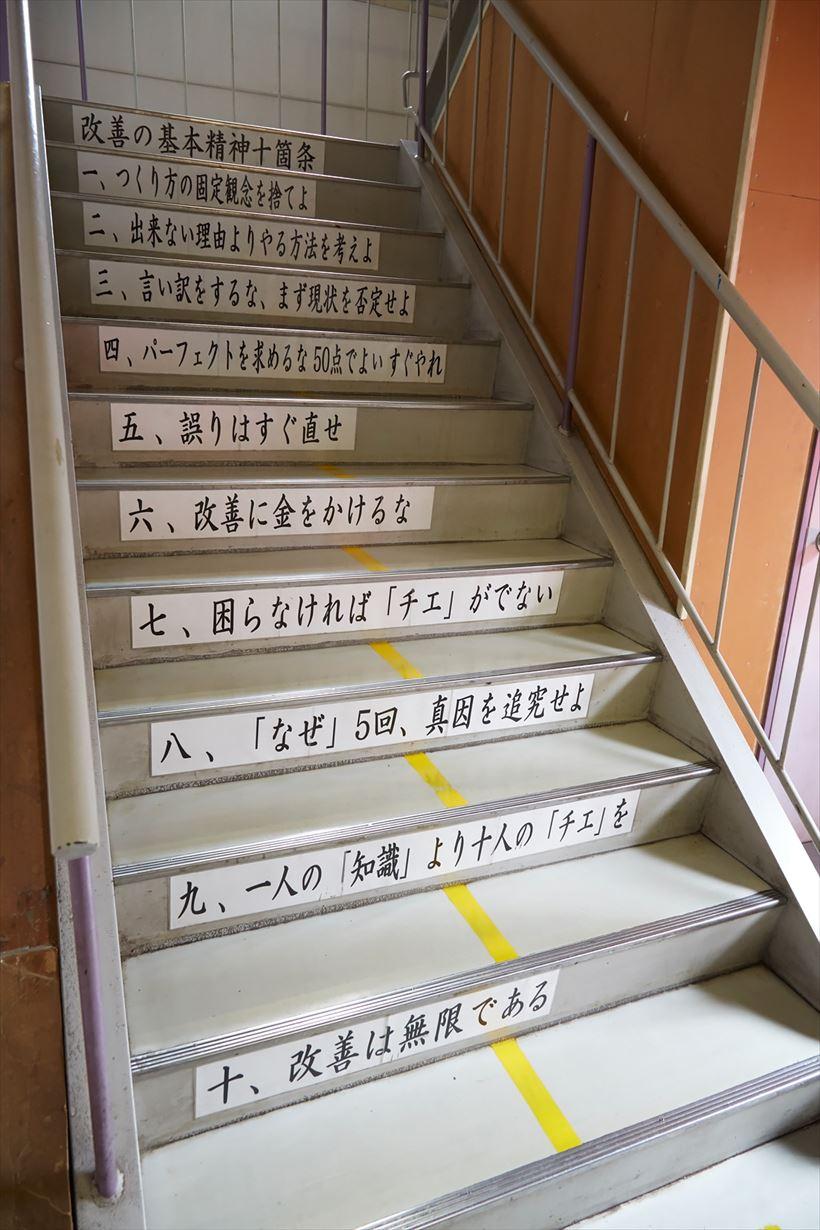 ↑工場1階と2階をつなぐ階段。一段一段に同社の「改善の基本精神十箇条」が掲示されています