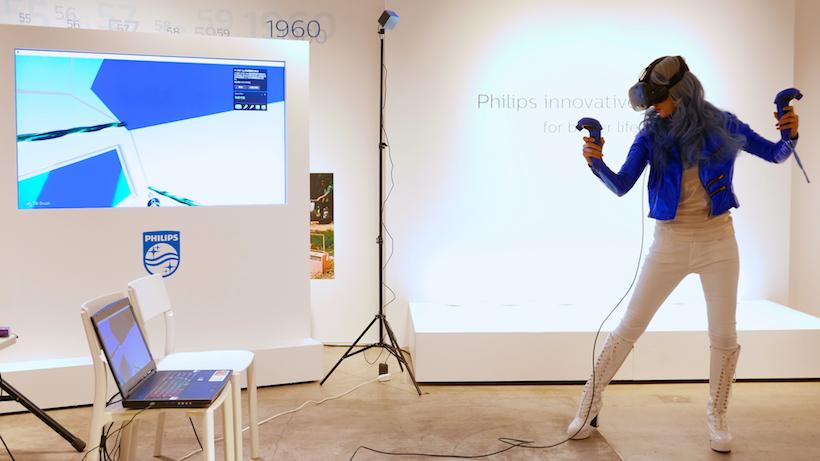 ↑VRアーティスト・せきぐちあいみ氏。両手のコントローラーを自在に操りながら、ディスプレイの中にフューチャリスティックな空間を創出していく