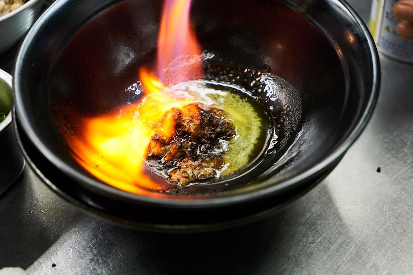 """↑これが「麺家うえだ」の代名詞といえる、""""焦がし""""のラーメン。牛脂のミンチをベースにした甘味のあるオイルにニンニクなどを効かせ、炎上するほど豪快に炙る。演出だけではなく、香ばしい風味付けとしてもこの所作は欠かせない。スモーキーで、なんとも「Rock」な味わいが生まれる"""