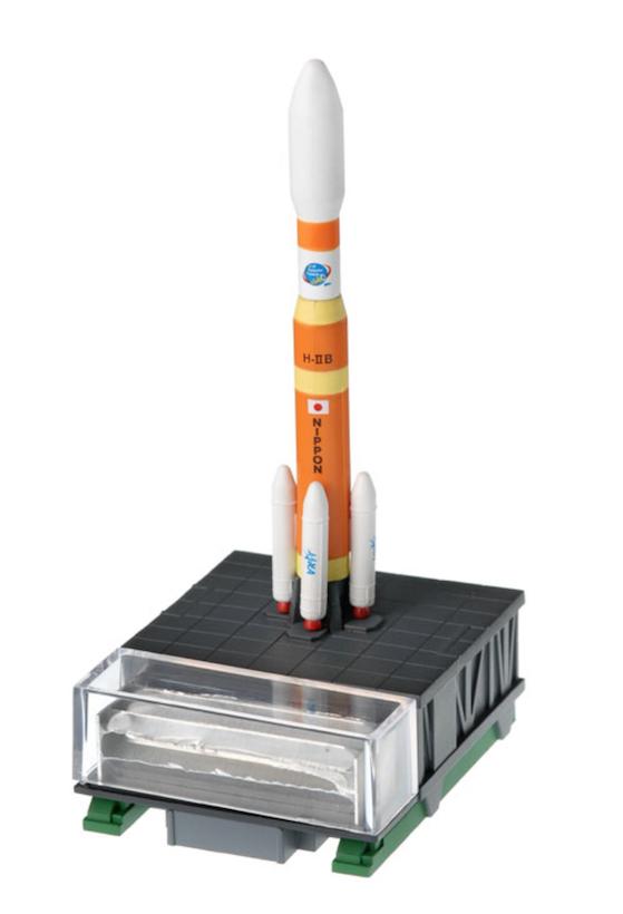 """↑2009年に種子島宇宙センターから打ち上げられ地球に帰還した「H-ⅡBロケット」のパーツ""""フェアリング""""のなんと実物を封入! H-ⅡBロケットフィギュアのディスプレイの土台部分に収納できる"""