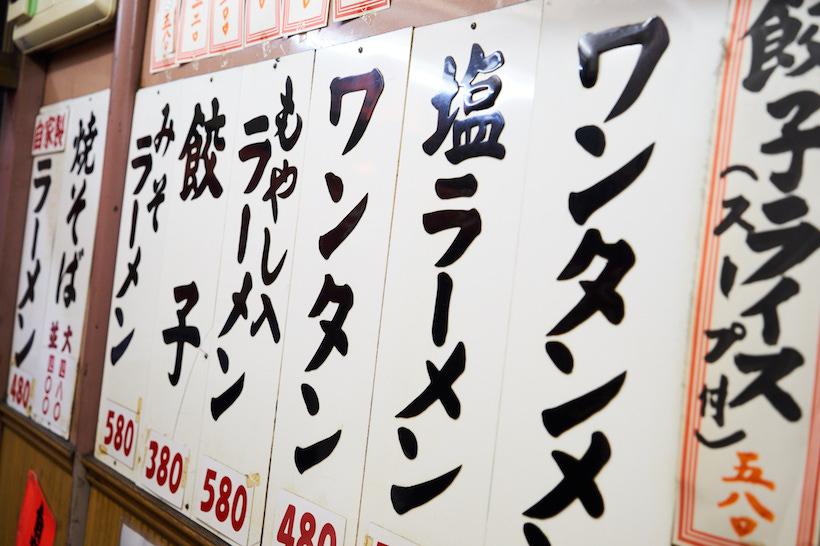 ↑昭和の情緒あふれる店内はカウンターのみで、壁にはメニューがズラリ。価格も、まるで時が止まったかのように安い
