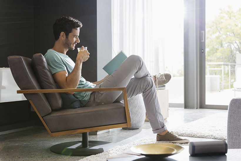 Man drinking tea and reading book in living room