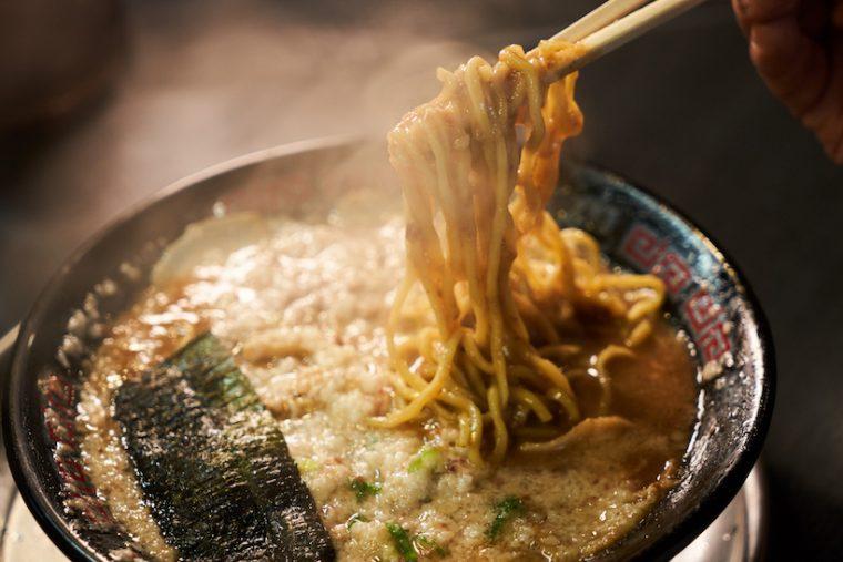 ↑ジュレのようなスープをしっかり絡めて持ち上げる麺は約130g。大盛や替玉は150円となり、替玉の場合は自家製のストレート細麺を選ぶこともできる