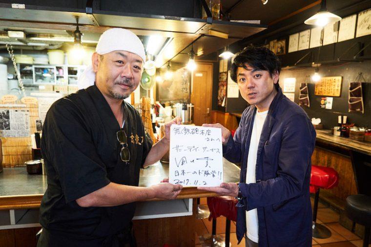 ↑赤迫さんへ色紙でメッセージを贈る田中さん。「みんなに自慢しよっと!」と、赤迫さんも笑顔でパシャリ。色紙には「日本一のド豚骨!」との田中さんの一筆が!