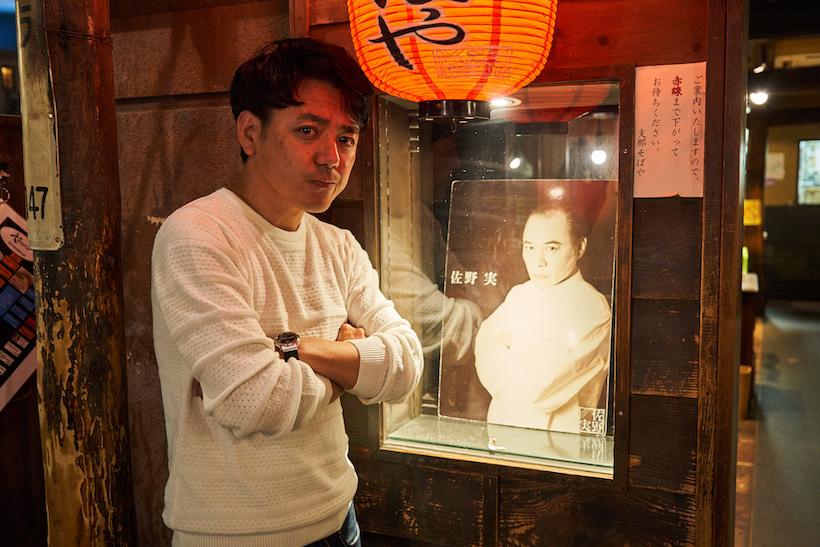 ↑入口の脇に飾られた佐野 実さんの写真と一緒に。田中さんももちろん生前のご本人に会ったことがあり、佐野さんを慕う多くのラーメン店主とも仲がいい