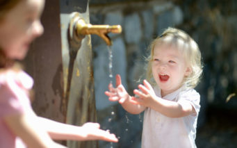 40946753 - two sisters having fun with drinking water fountain in italy
