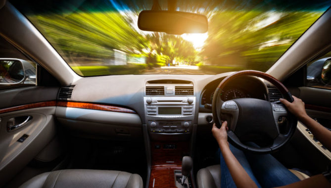 30996125 - hands on steering wheel of a car and motion blurred asphalt road and sky