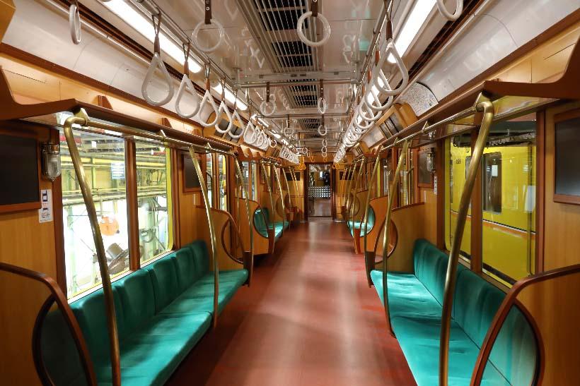 ↑車内の内装は木製色の化粧板をメインに。座席も通常車両の煉瓦柄に対して緑色のシートモケット、手すりは真鍮色とされている