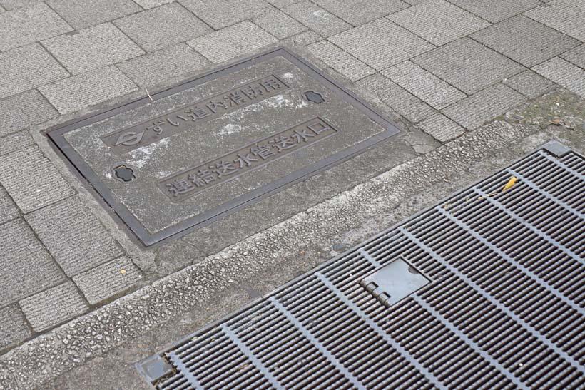 ↑中央通りの歩道上に通気孔があり、下に旧萬世橋駅が眠る。通気孔の横には旧営団地下鉄の社章が入った消防用の送水口があった