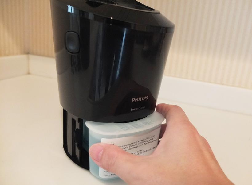 ↑洗浄充電器側面の着脱ボタンを押して本体を上部に上げ、クリーニングカートリッジを前面から装着します