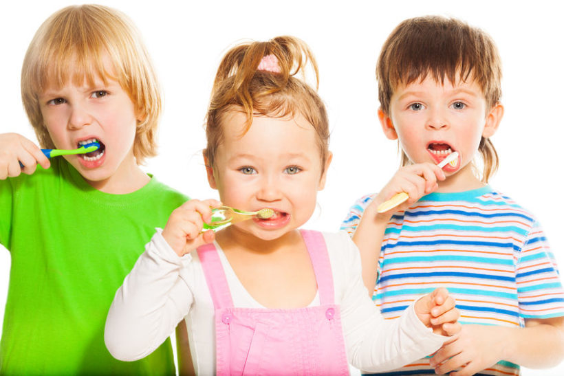 26599688 - three happy little 3-4 years old kids standing with toothpaste
