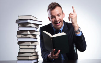 27838323 - young business man reading at an office with a stack of books and pointing up with a smile on his face, as he understands the idea. on a light studio background