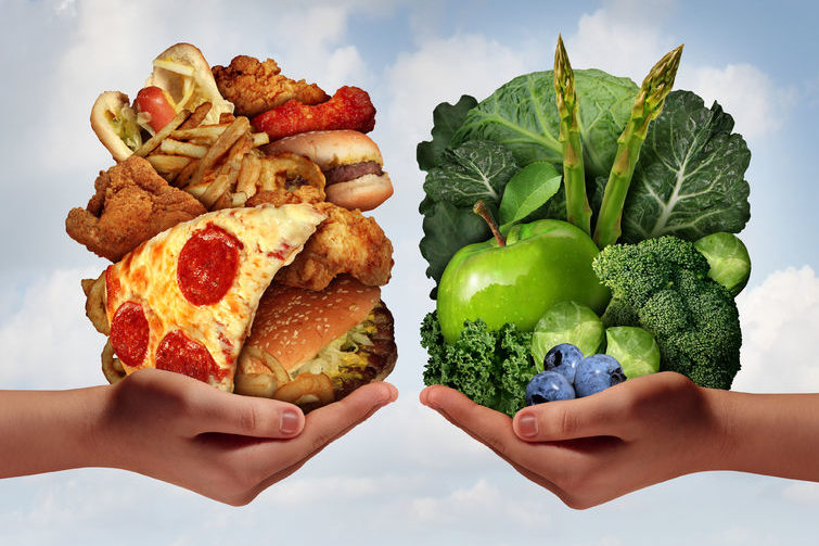 31815607 - nutrition choice and diet decision concept and eating choices dilemma between healthy good fresh fruit and vegetables or greasy cholesterol rich fast food with two hands holding food trying to decide what to eat.