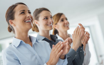 44655773 - cheerful confident business women applauding and smiling, success and achievement concept