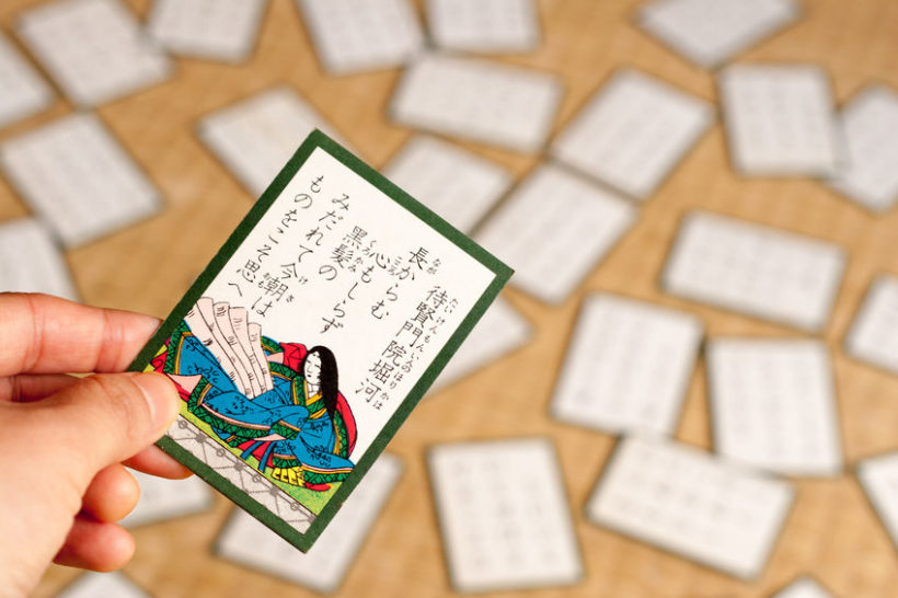 53101612 - a japanese traditional card game called hyakunin isshu, holding a card by a hand