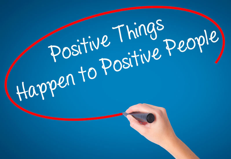 63666342 - women hand writing positive things happen to positive people with black marker on visual screen. isolated on blue. business, technology, internet concept. stock photo