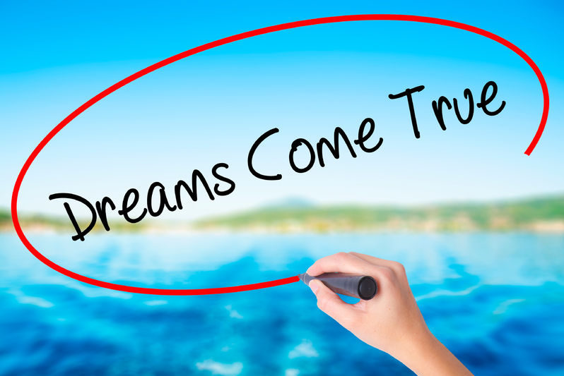 65142161 - woman hand writing dreams come true on blank transparent board with a marker isolated over water background. business concept. stock photo