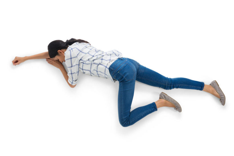 83349262 - unconscious woman lying on white background