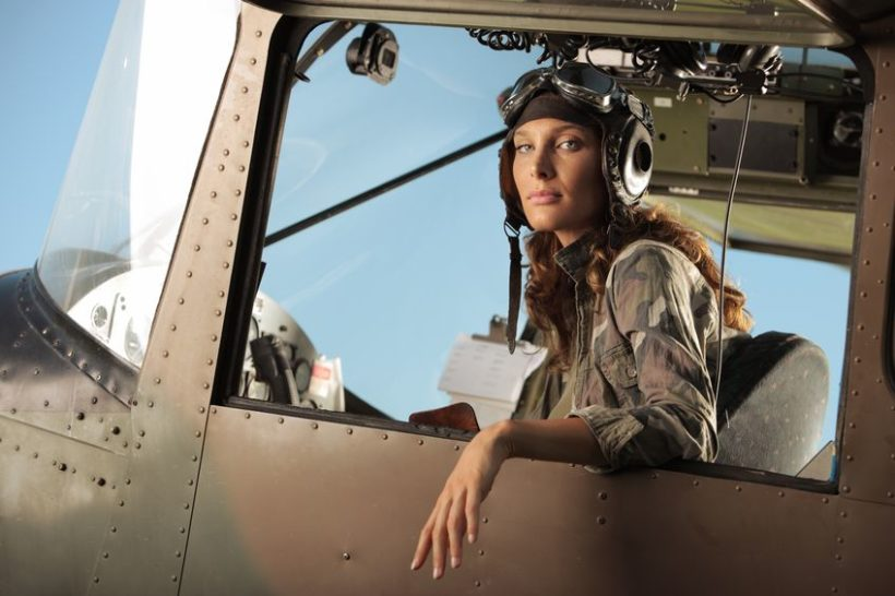 15075591 - portrait of young woman pilot in a military airplane