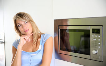 24761915 - portrait of woman by microwave oven