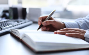 30608079 - businessman writes in a notebook while sitting at a desk