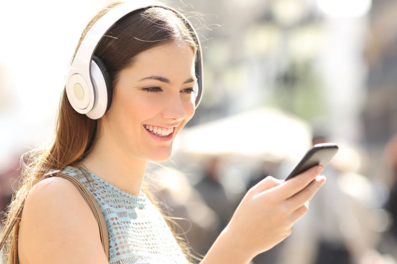 37920469 - woman listening wireless music with headphones from a smart phone in the street