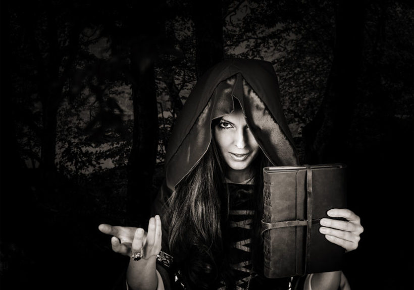 45234889 - beautiful young halloween witch wearing vintage gothic dress with hood holding magical book of spells in old leather cover in dark night forest