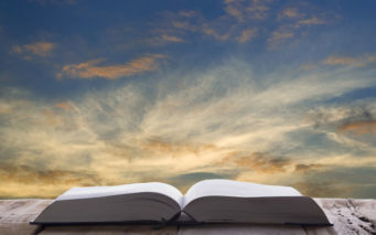 56685766 - open book on wood table and sunset as background