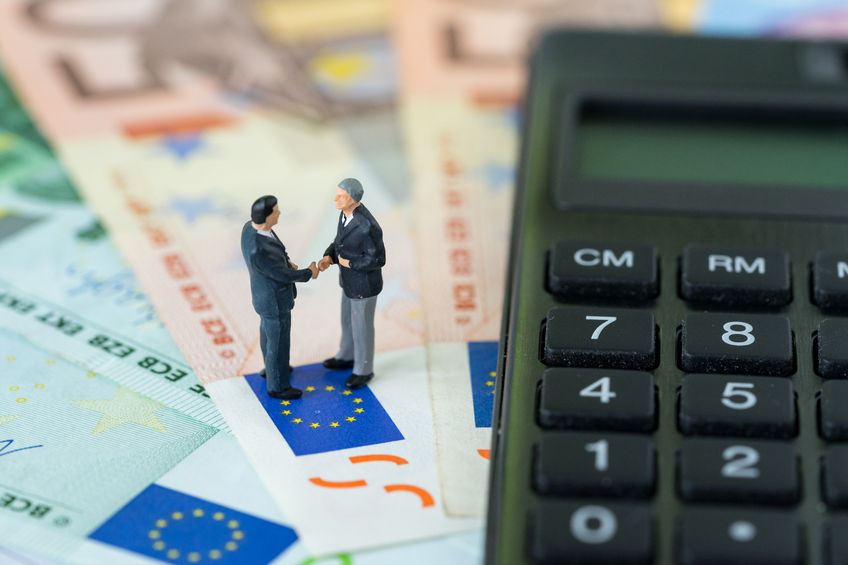 90609986 - miniature figure, businessmen shaking hand standing on pile of euro banknotes with calculator as euro economy agreement or brexit negotiation concept.