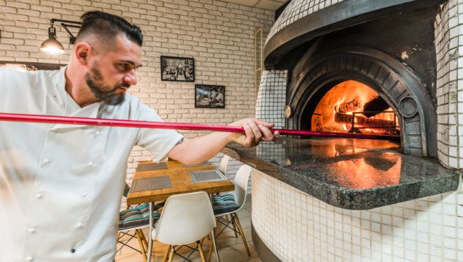 91210314 - handsome pizzaiolo man baking pizza in woodfired oven in local pizzeria