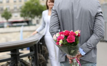 14679358 - man ready to give flowers to girlfriend on a bridge