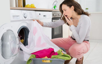 44592107 - shock young woman looking at stained cloth in kitchen