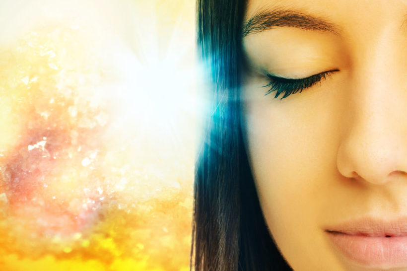 59199205 - macro close up of young woman meditating with eyes closed.conceptual spiritual background with light beam.