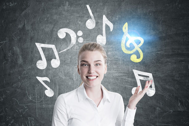 83413493 - close up of a happy young blonde music teacher standing near a blackboard and pointing at music notes drawn on it. toned image