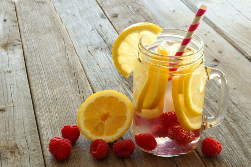 39372911 - vitamin water with lemon and raspberries in a jar with straw against a wood background