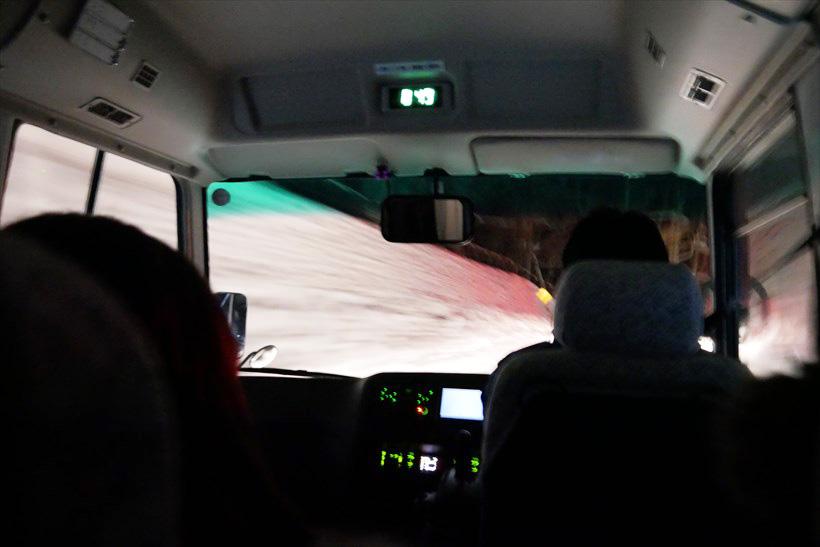 ↑氷瀑を目指して山道を進むツアーのバス。バスの両脇には雪の壁が