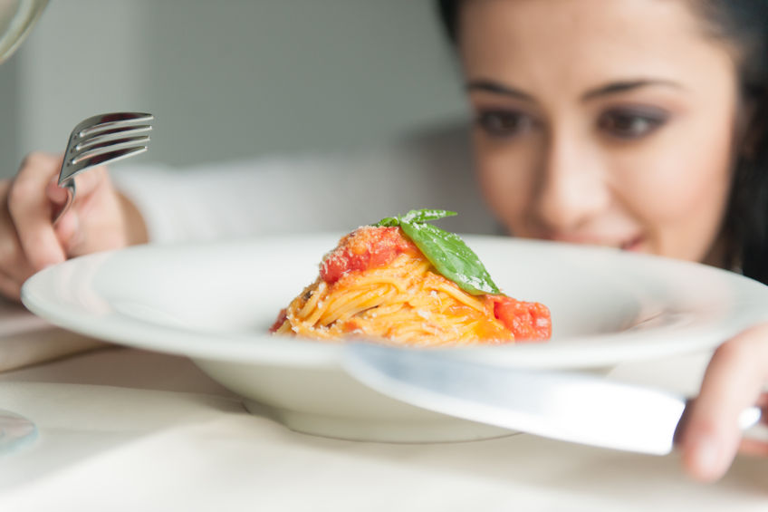 31750737 - closeup of woman's hands holding fork and knife. young girl looking at food in restaurant