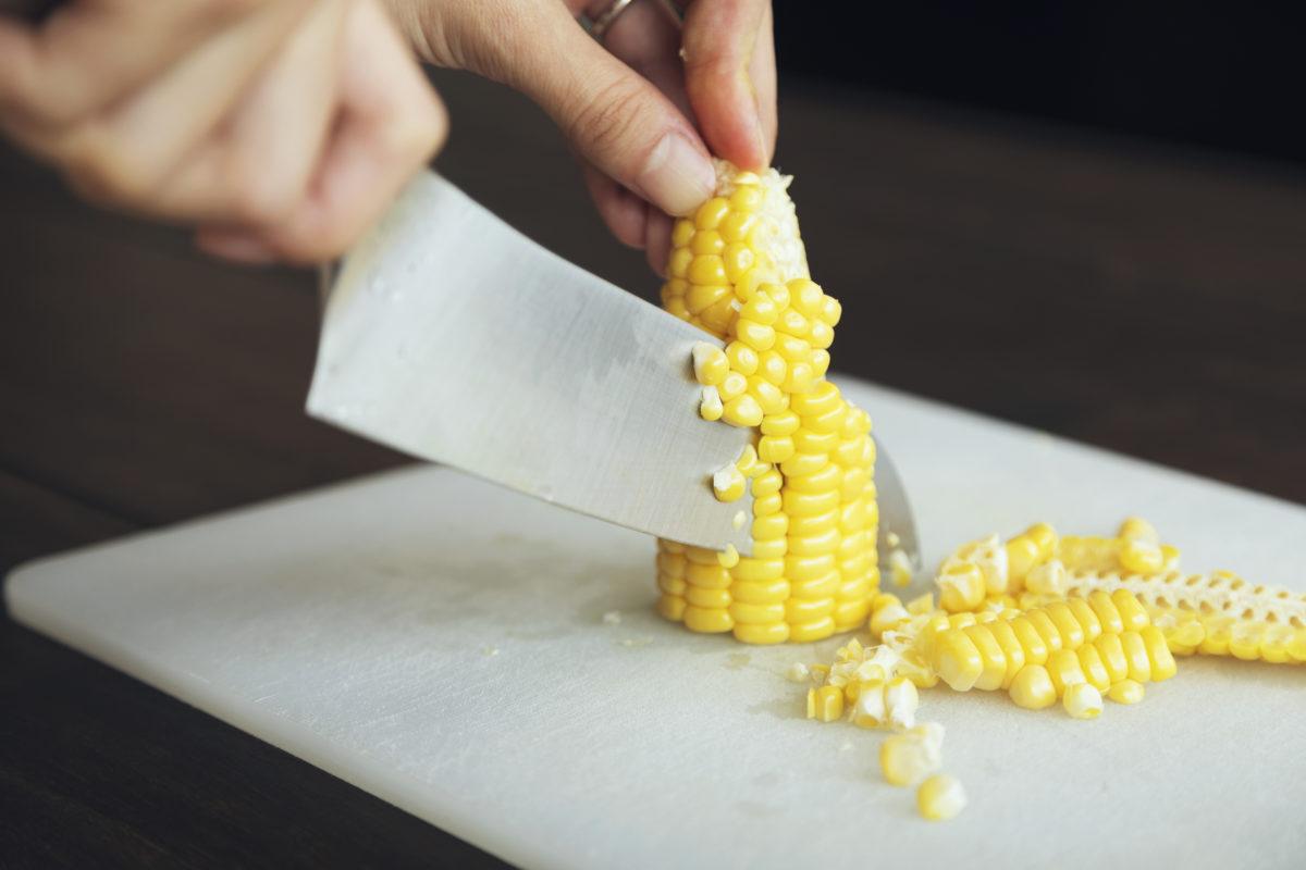 ①生のとうもろこしの実を包丁で削いでいく