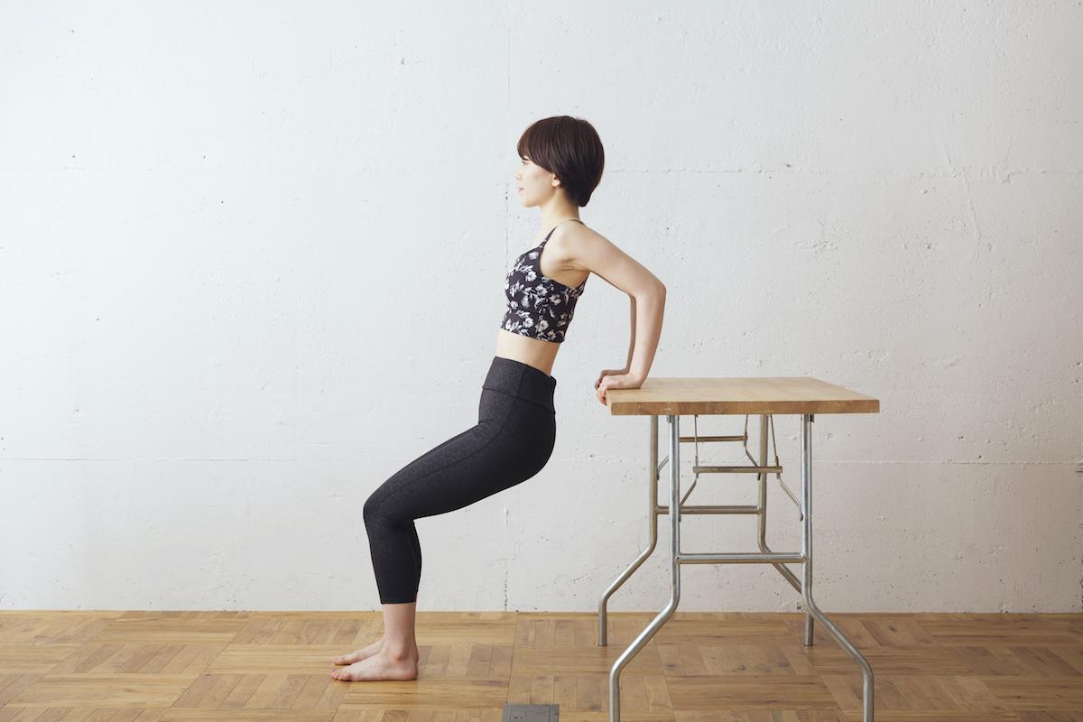 ①机を背にした状態で少し離れた位置に立ち、机のふちをつかむ
