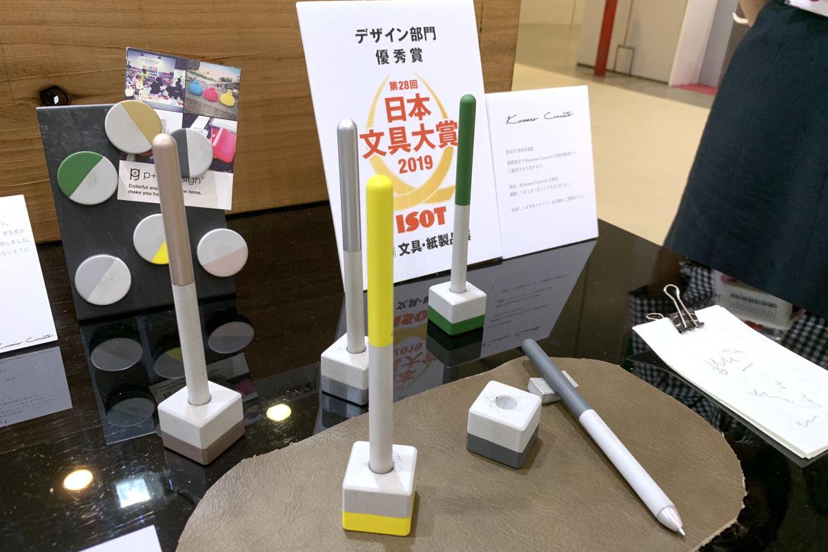 ↑デザイン部門優秀賞のピージーデザイン「Kuramae Concrete Pen」。専用ペンスタンドも付属する