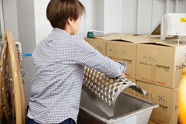 ↑醸造所で作業をする須合さん。例えば除梗破砕機はイタリア製の小型のものを使用するなど、道具は女性の須合さんでも使いやすいものを選んでいる