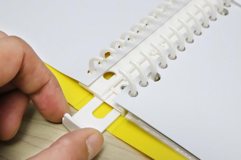 ↑ファイルのリングは、下のスライダーを引くと開き、押し込むと閉じる構造。プラ製のわりに堅実な作動感があって、よくできている