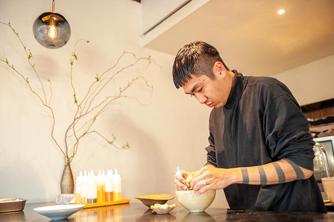 ↑食材を盛り付けるシェフの安田さん。あたたかみを感じる陶器の食器に、すべての食材がそれぞれに映えるよう、ピンセットまで駆使しながら盛り付けていく