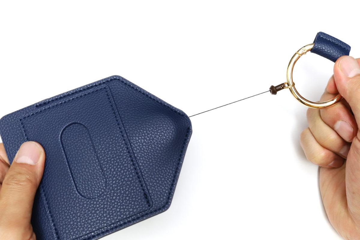 ↑合皮製のケースからリングを引っぱると紐(リール)が伸び、手を離すと自動で巻き取られ戻る