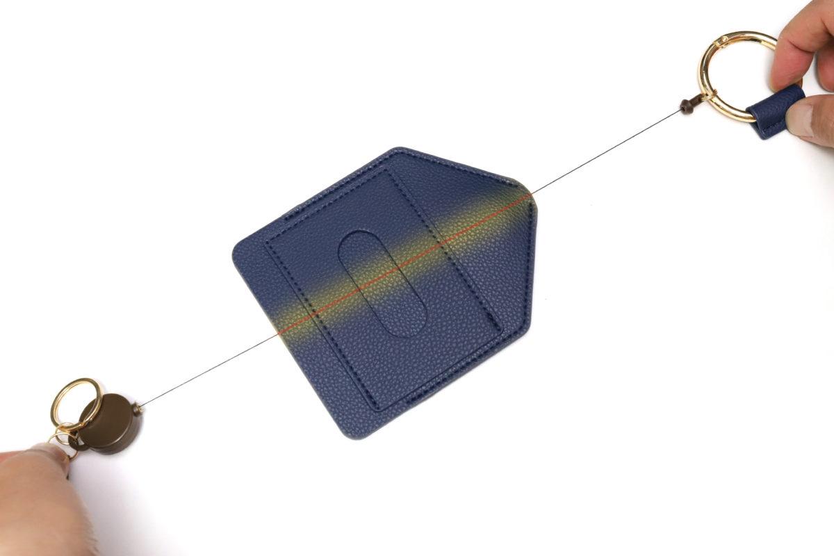 ↑パスケースの中をカラビナリングからリールまでのヒモが素通しになっているという構造。なるほど!